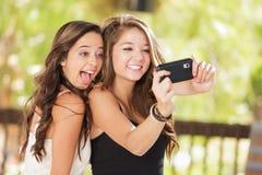 Novias adolescentes de la raza mixta juguetona que usan su célula elegante Pho Imagen de archivo