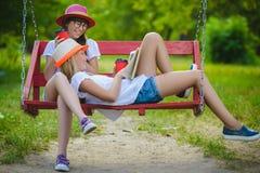 Novias alegres que se divierten en el oscilación al aire libre Concepto de la amistad Imagen de archivo libre de regalías
