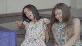 Novias atractivas del retrato dos que se sientan en las escaleras después de hacer compras con los bolsos de compras Las señoras  metrajes
