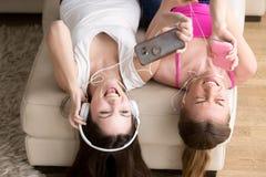 Novias emocionadas que disfrutan de música en auriculares Fotografía de archivo