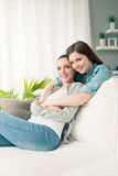 Novias que abrazan en el sofá Fotos de archivo