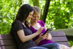 Novias que comparten un etablet en el banco de parque, horizontal Imagenes de archivo