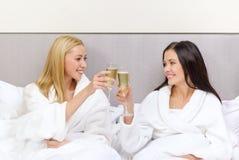 Novias sonrientes con los vidrios del champán en cama Imagenes de archivo