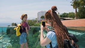 Novias turísticas del viaje que se divierten que toma la foto con smartphone en la ciudad vieja de Europa metrajes