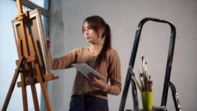 Young brunette is drawing by paintbrush, holding palette and standing near easel. Novice artist is learning drawing by oil painting on a canvas. Young girl with stock video