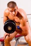 Novice bodybuilder training. His bicep royalty free stock photo
