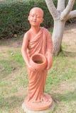 Novice bouddhiste tenant la poupée d'argile de cuvette d'aumône au temple bouddhiste thaïlandais photographie stock libre de droits