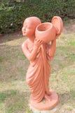 Novice bouddhiste tenant la poupée d'argile de cuvette d'aumône au temple bouddhiste thaïlandais images libres de droits