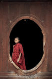 Inle Lake, Myanmar, young Buddhist monk at a monastery standing at oval window Royalty Free Stock Photo