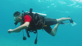 Novice diver learns to swim with scuba diving. Side view stock video