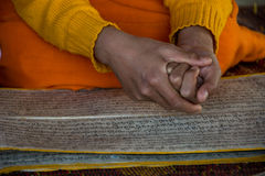 Novice monk at afternoon prayers with hands over sanskrit text Stock Image