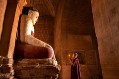 Novice monk praying with candles in front of buddha statue. Novice monk praying with candles in front of buddha statue inside old pagoda, Bagan Myanmar stock images
