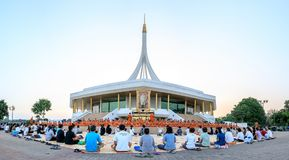 Novice monk or priest and people sitting for meditation at Ratchamangkhala Pavillion of public park name Suan Luang Rama IX on eve. Bangkok, Thailand. - April 23 royalty free stock images