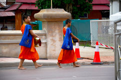 Novice monk procession walking on the road for people pray and p. Ut food offerings at Nam city in morning time on July 26, 2016 in Nan, Thailand stock photography
