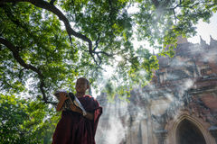 Novice monk read the book in front of Sulamani Pagodas. BAGAN, MYANMAR - DEC 13, 2015: novice monk read the book in front of Sulamani Pagodas. Bagan on December stock photos