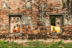 Novice monk reading books in ruins.