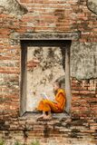 Novice monk reading books in ruins at Putthaisawan temple.