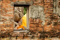 Novice monk reading  books in ruins at Putthaisawan temple. Stock Photos
