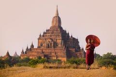 Novice monk with red umbrella walking in front of Sulamani Pagodas. BAGAN, MYANMAR - DEC 13, 2015: Novice monk with red umbrella walking in front of Sulamani stock photos