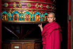 Novice monk rotating prayer wheel, Kathmandu, Nepal. THAMEL, KATHMANDU, NEPAL - OCTOBER 18, 2015 : Novice monk rotating a large praying wheel in a temple in royalty free stock photo