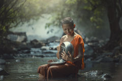 Novice with monk's alms bowl stock photography