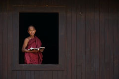 Novice monk smiles at the old temple window Stock Photo