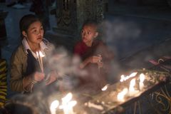 Novice monk and woman lighting candles at a Buddhist temple stock images
