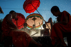 Novice monks beating a new dry with palm reeds and splashing water. Young novice monks in Luang Prabang are beating a drum with palm reeds and splashing water in stock photo