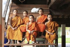 Novice monks sitting on stairs. Mae Hong Son,Thailand - August 17, 2013 : Novice monks sitting on stairs at wooden monk's house after reading book in Mae Hong stock photography