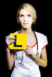 Novice nurse or medical student. Beware of a beautiful blonde female novice nurse or medical student with a look of trepidation on her face at her new career Royalty Free Stock Photography