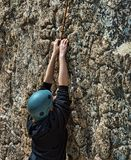 Novice rock climber hanging on rocky cliff stock images