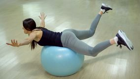 Novice in sports. Young woman doing exercises with gymnastic ball.  stock image