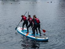 Novice students learn stand up paddle boarding at Salford Quays in Manchester, UK. Manchester, United Kingdom - April 24, 2019: Novice students learn stand up royalty free stock photos
