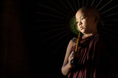 Novice with umbrella. A Young novice monk holding an umbrella stock image