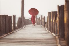 Novice walk on u bein wooded bridge. In morning time, Mandalay city, Myanmar Stock Images