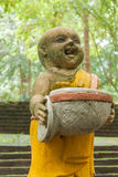Novices statue. Old novices statue, staue hold an alms bowl and laugh Royalty Free Stock Images