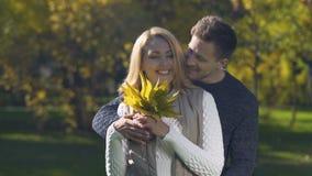 Novio blando que presenta el ramo de hojas de otoño a la novia, divirtiéndose almacen de video