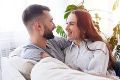 Novio cariñoso y novia que miran uno a mientras que sitt Imagenes de archivo