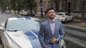 Novio cerca del coche deportivo en la calle Camisa rosada, corbata de lazo, chaqueta azul Hombre de negocios almacen de metraje de vídeo