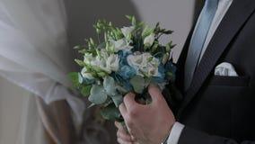 Novio con casarse el ramo en sus manos en casa Camisa blanca, lazo azul, chaqueta almacen de video