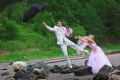 Novio con el paraguas y la novia - broma de la boda Imagenes de archivo