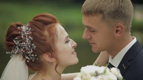 Novio con la novia cerca del lago en el parque Pares de la boda C?mara lenta metrajes