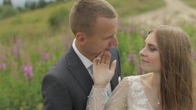 Novio con la novia junto en un claro de flores Pares de la boda Familia feliz almacen de video