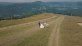 Novio con la novia que camina junto en las colinas de una montaña Tiro a?reo del abej?n almacen de video