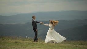 Novio con la novia que se divierte en las colinas de una montaña boda La novia está bailando metrajes
