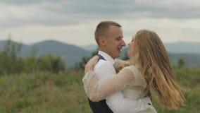 Novio con la novia que se divierte en las colinas de una montaña Pares de la boda Familia feliz metrajes