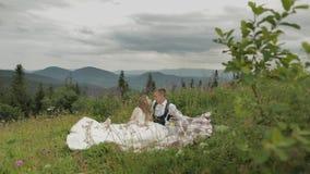 Novio con la novia que tiene una comida campestre en las colinas de una montaña Pares de la boda Familia metrajes