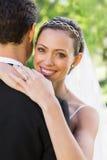 Novio de abarcamiento de la novia feliz en jardín Foto de archivo