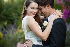 Novio de abarcamiento de la novia feliz mientras que se coloca en parque Fotografía de archivo libre de regalías