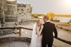 Novio de abarcamiento de la novia mientras que coloca las barandillas cercanas Imagen de archivo